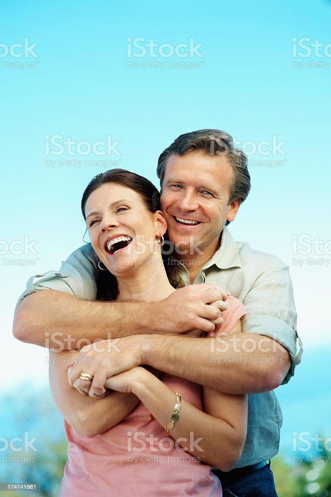 Smiling mature man hugging cute woman against blue background stock photo