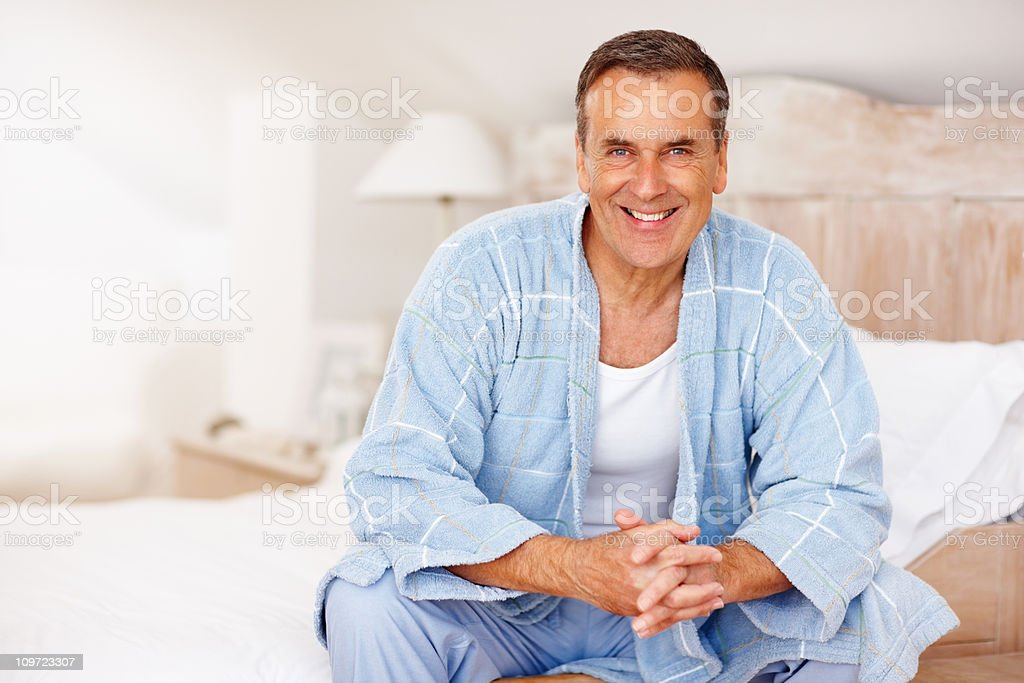Smiling mature man in bathrobe sitting on bed at home royalty-free stock photo