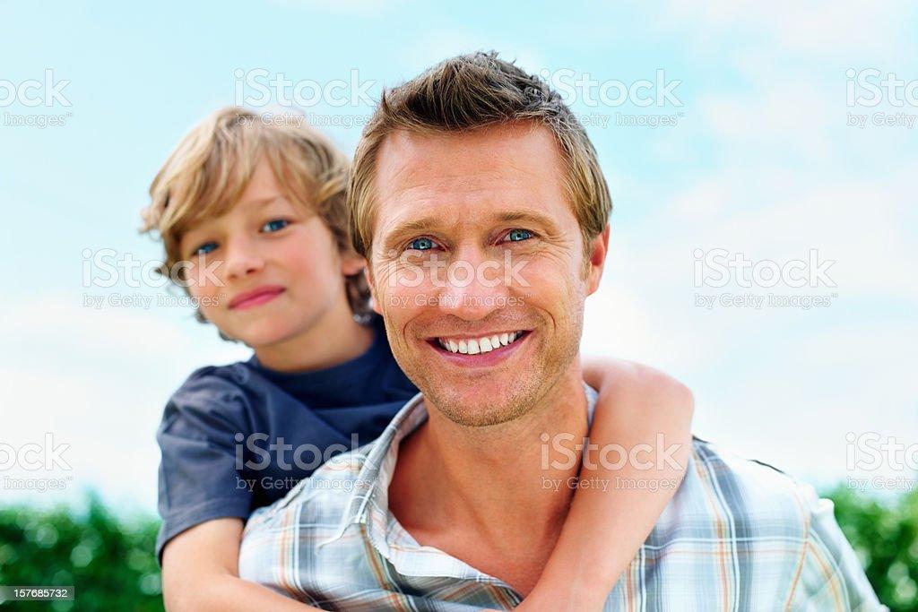 Smiling mature man piggybacking his son royalty-free stock photo