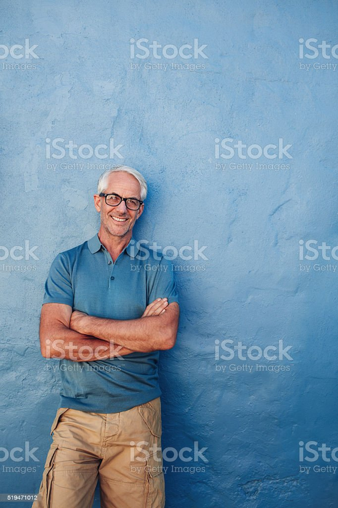 Smiling mature man standing with his arms crossed stock photo