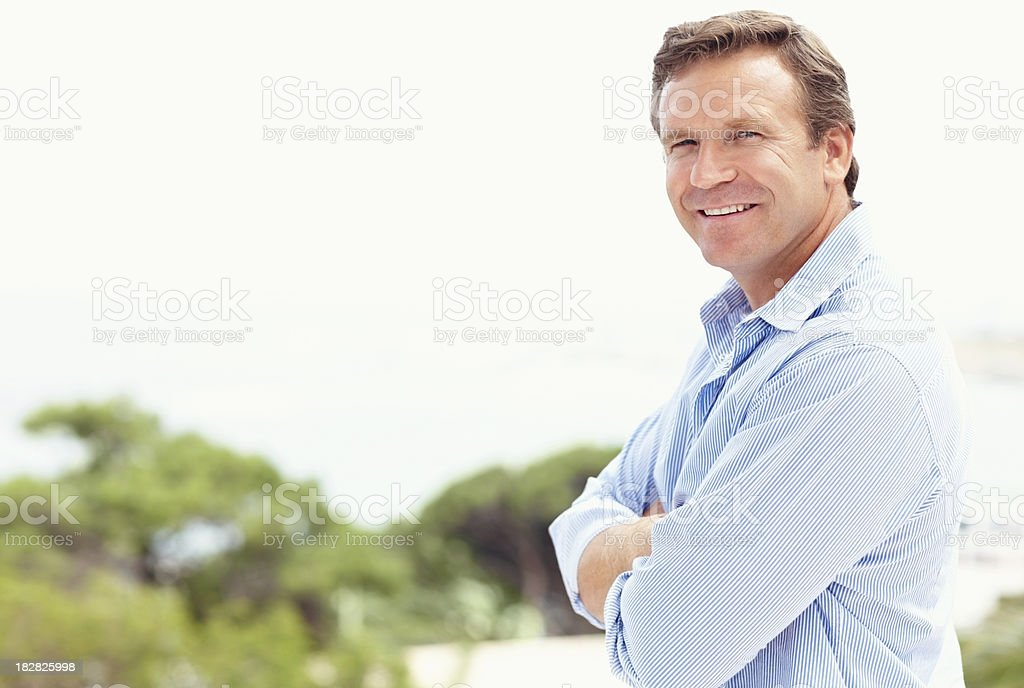 Smiling mature man with arms crossed standing outdoors royalty-free stock photo