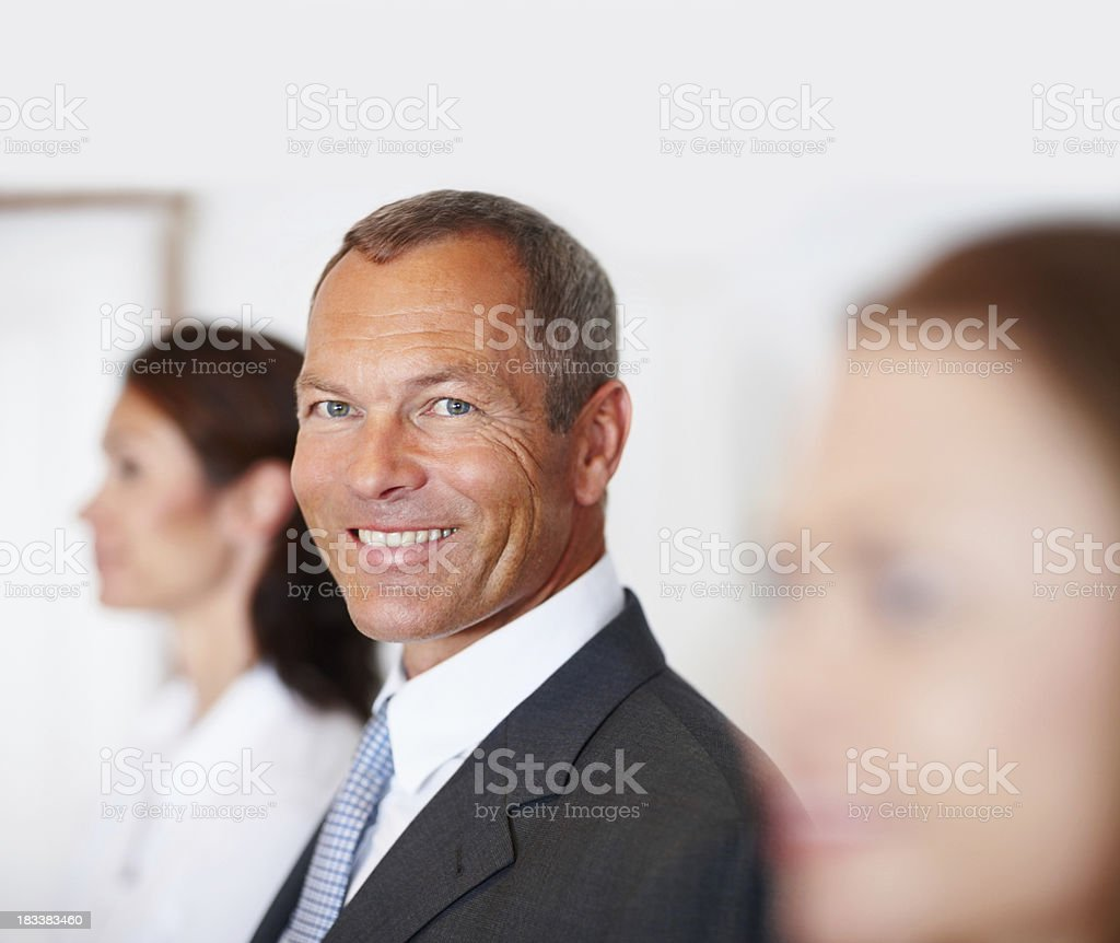 Smiling mature man with business colleagues in office royalty-free stock photo