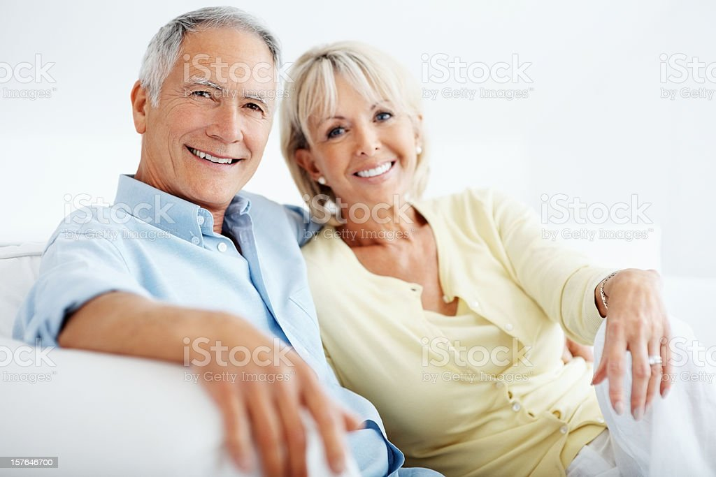Smiling mature man with his wife sitting together on sofa royalty-free stock photo