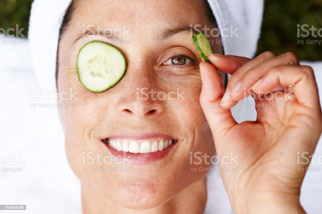 Smiling mature woman getting beauty treatment stock photo