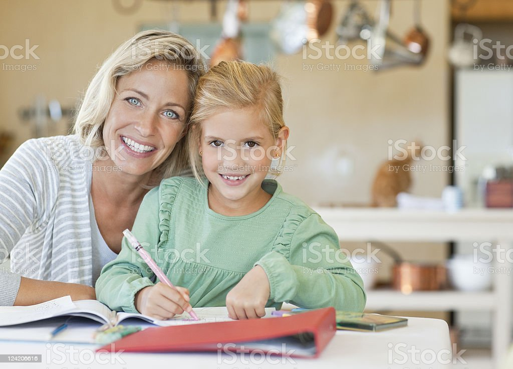 Smiling mature woman helping her daughter with homework royalty-free stock photo