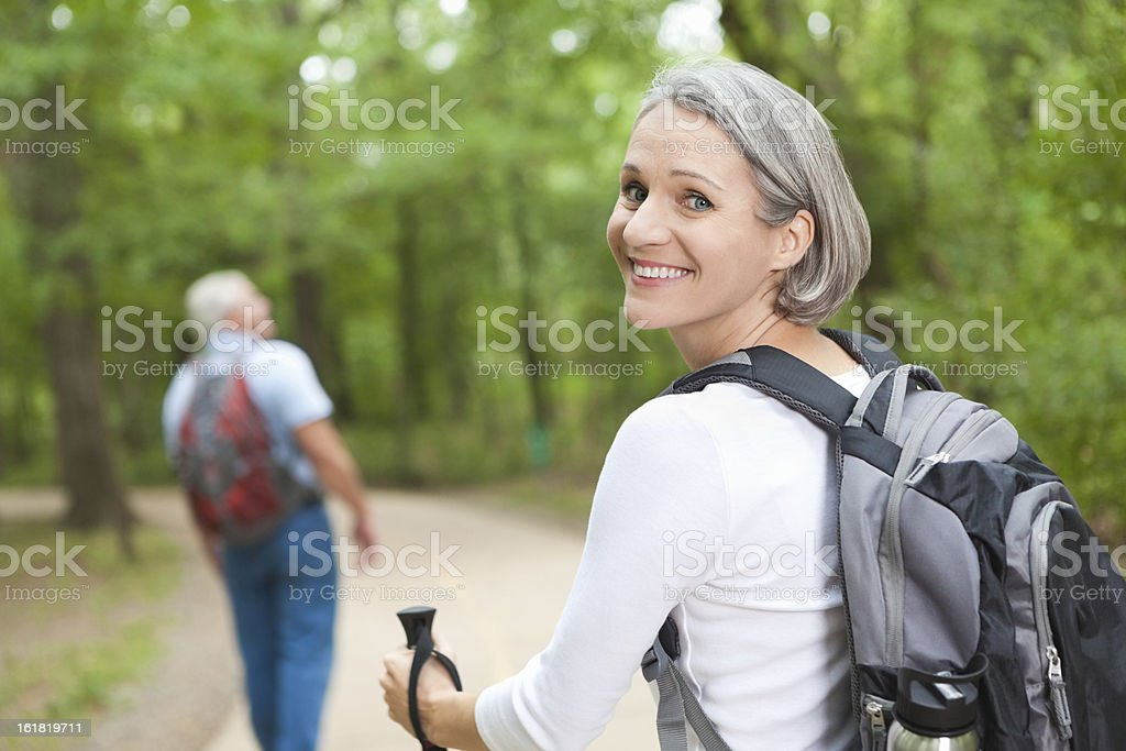 Smiling mature woman hiking on trail with husband royalty-free stock photo