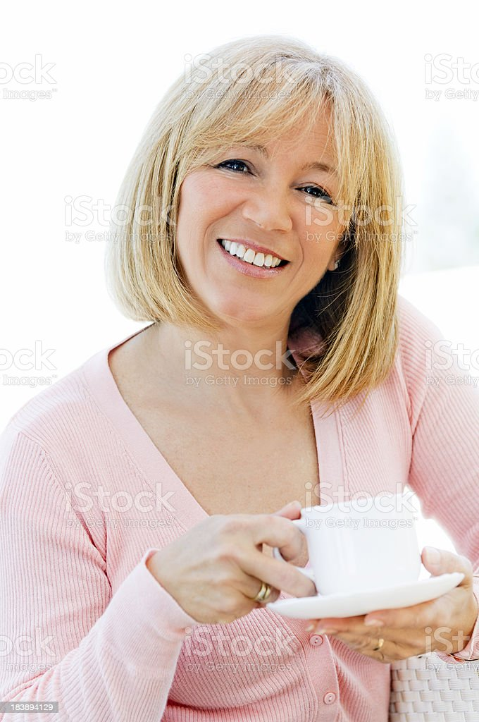 Smiling mature woman holding coffee cup stock photo