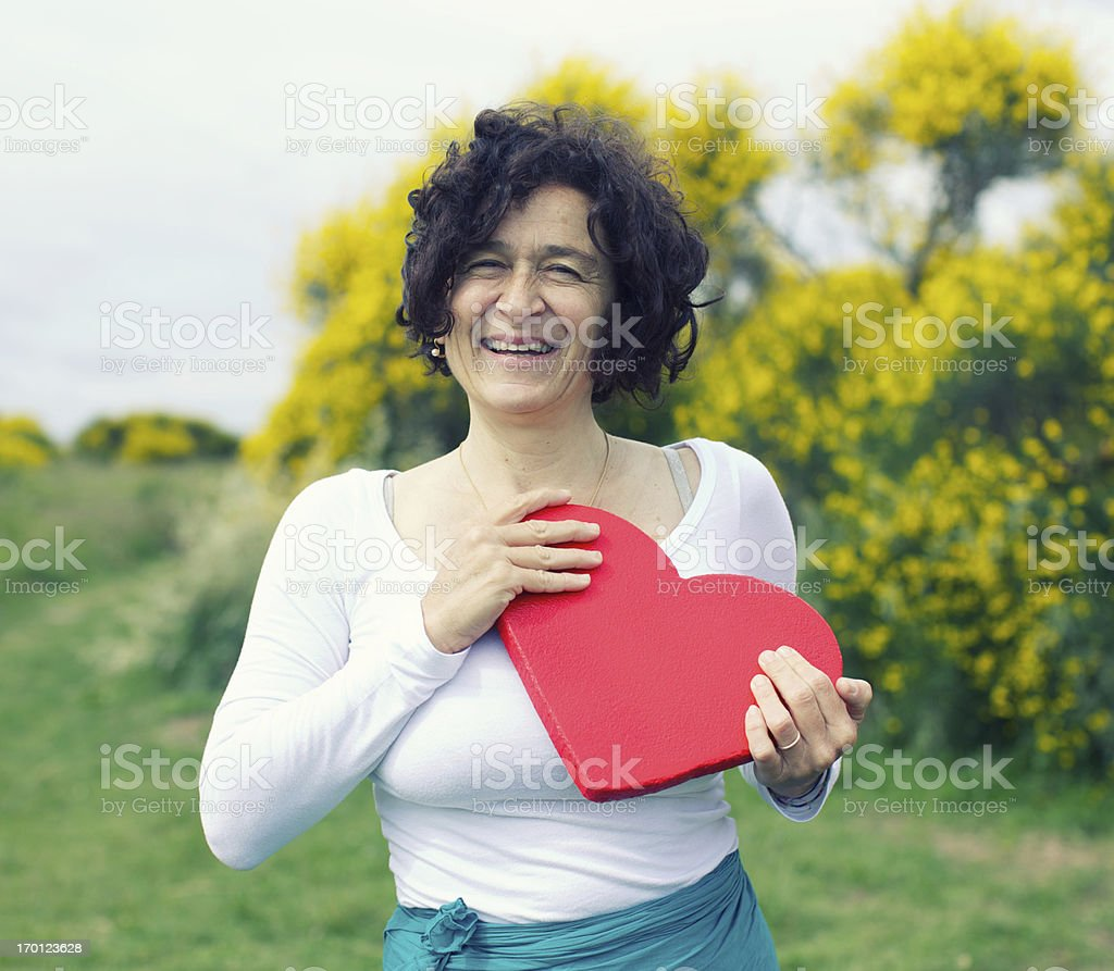 Smiling mature woman holding heart stock photo