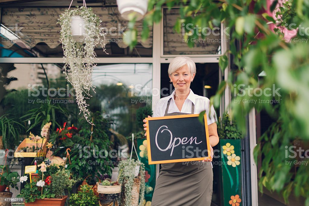 Smiling mature woman holding open sign at flower shop. stock photo