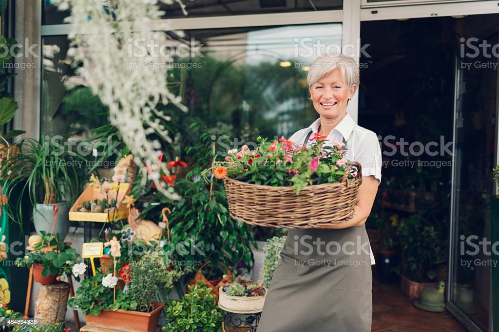 Smiling mature woman holding with flowers outside flower shop. stock photo
