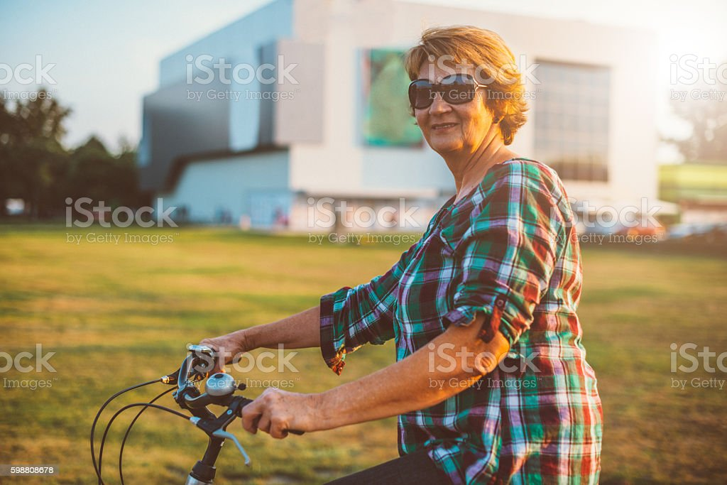Smiling mature woman in relaxing bicycle ride in city stock photo