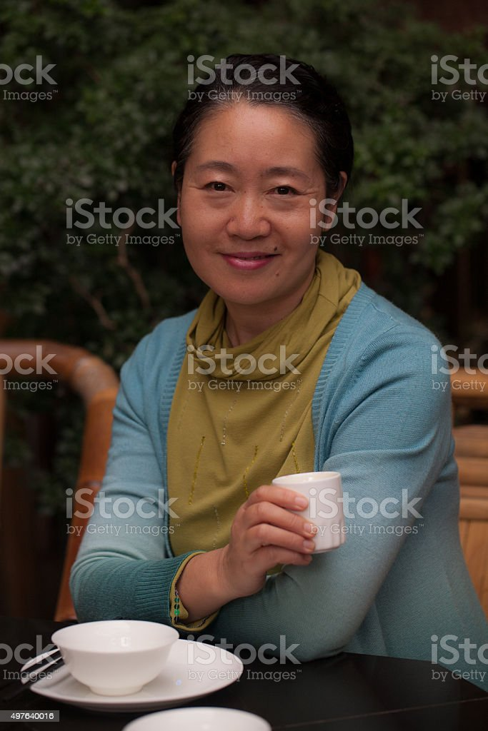 Smiling mature woman of East Asian ethnicity holding tea cup stock photo