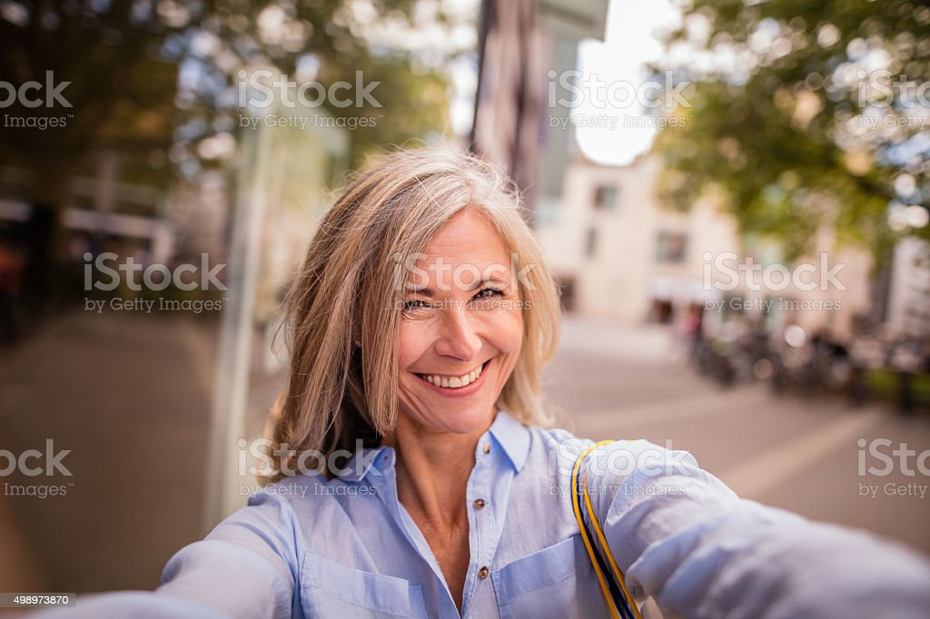 Smiling mature woman on a city street taking fun selfie stock photo