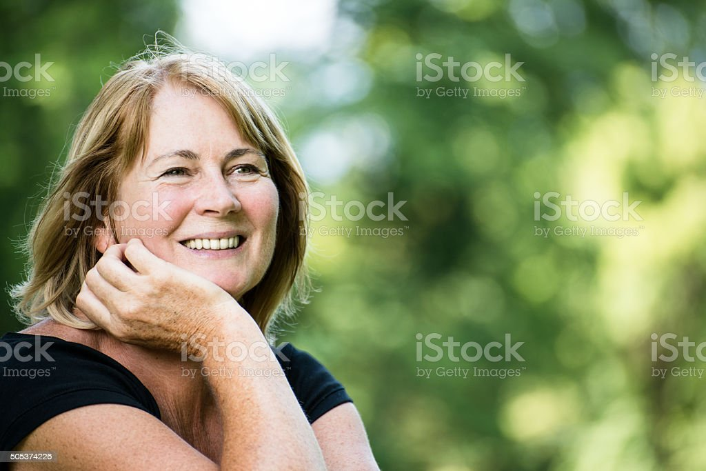 Smiling mature woman outdoor portrait stock photo