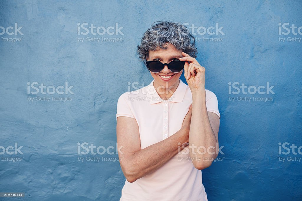 Smiling mature woman peeking over sunglasses stock photo