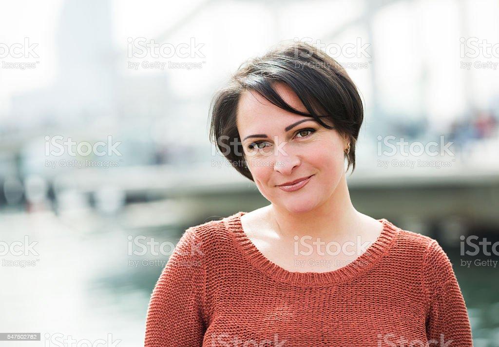 Smiling  mature woman posing outdoors stock photo