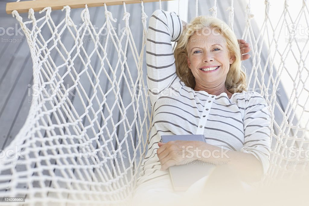 Smiling mature woman relaxing in hammock with a book royalty-free stock photo