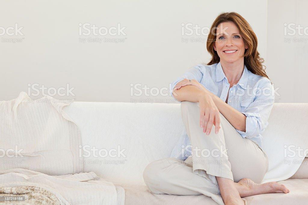 Smiling mature woman sitting on sofa stock photo