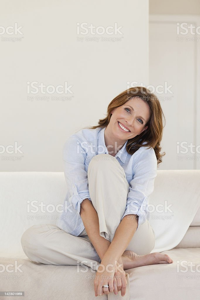 Smiling mature woman sitting on white couch stock photo