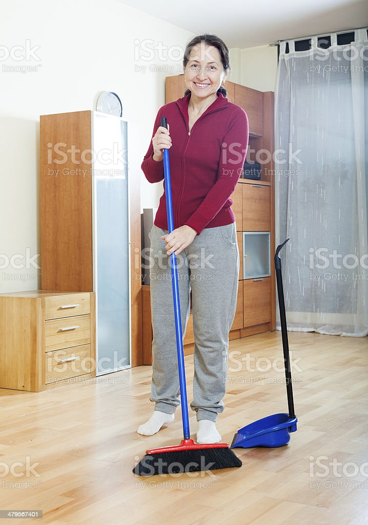 Smiling mature woman sweeping the floor stock photo