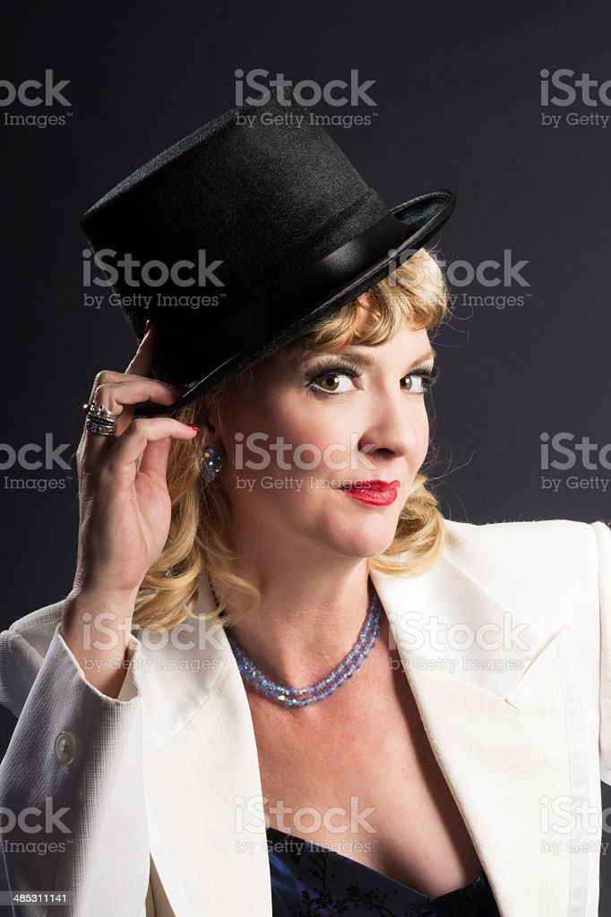 Smiling mature woman touching top hat. royalty-free stock photo