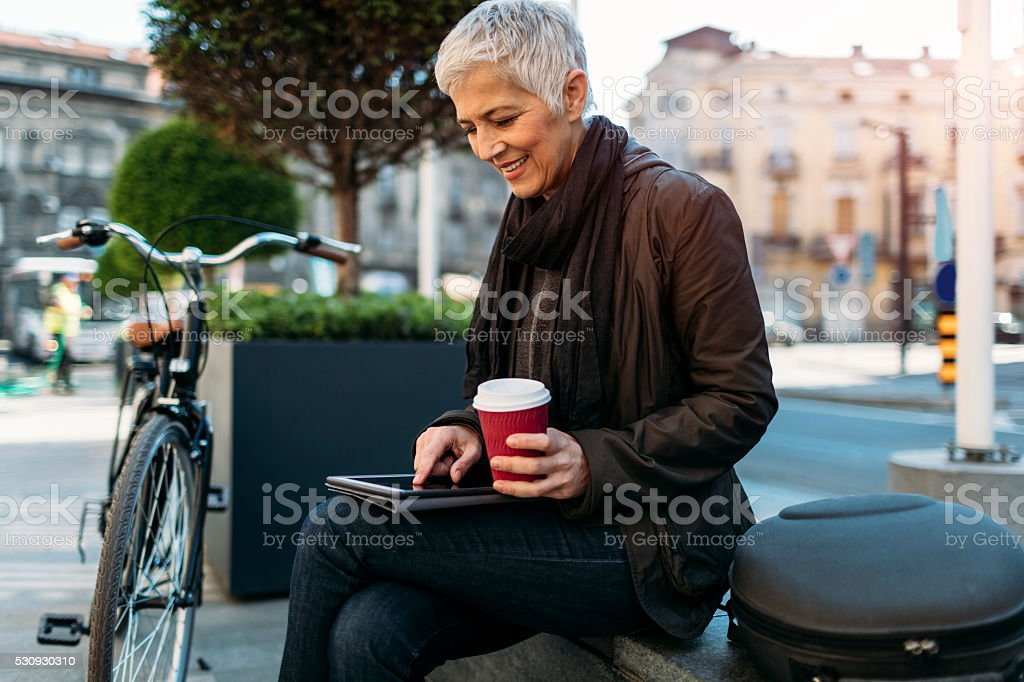 Smiling Mature Woman Using Digital Tablet Outdoors. stock photo