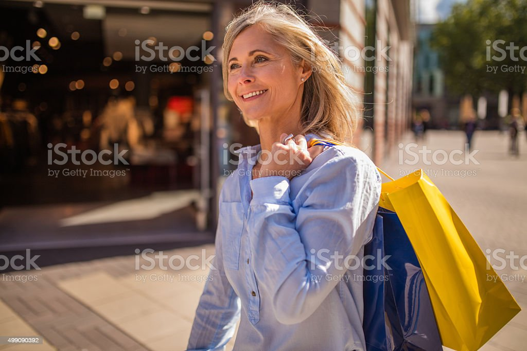 Smiling mature woman walking with shopping bags in town stock photo