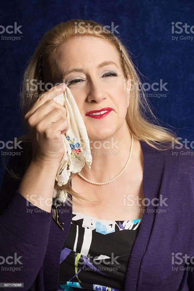 Smiling mature woman wiping tears of joy, waist up. stock photo