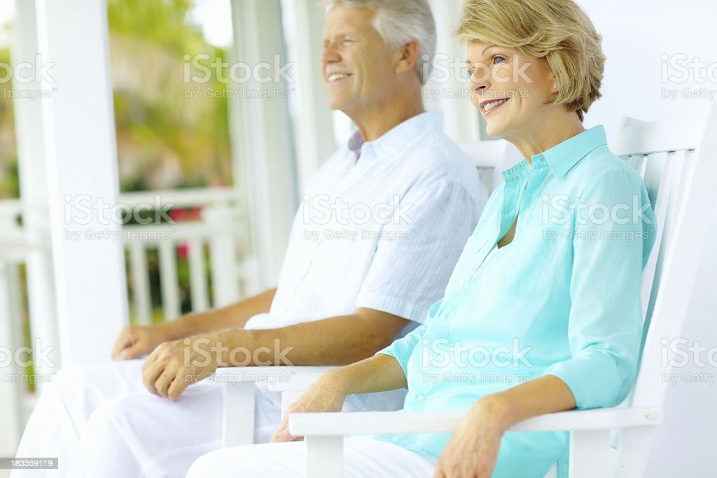 Smiling mature woman with her husband sitting in chairs royalty-free stock photo