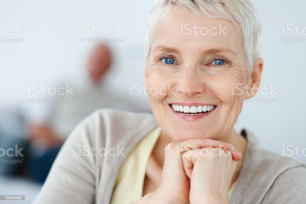Smiling mature woman with husband in the background royalty-free stock photo