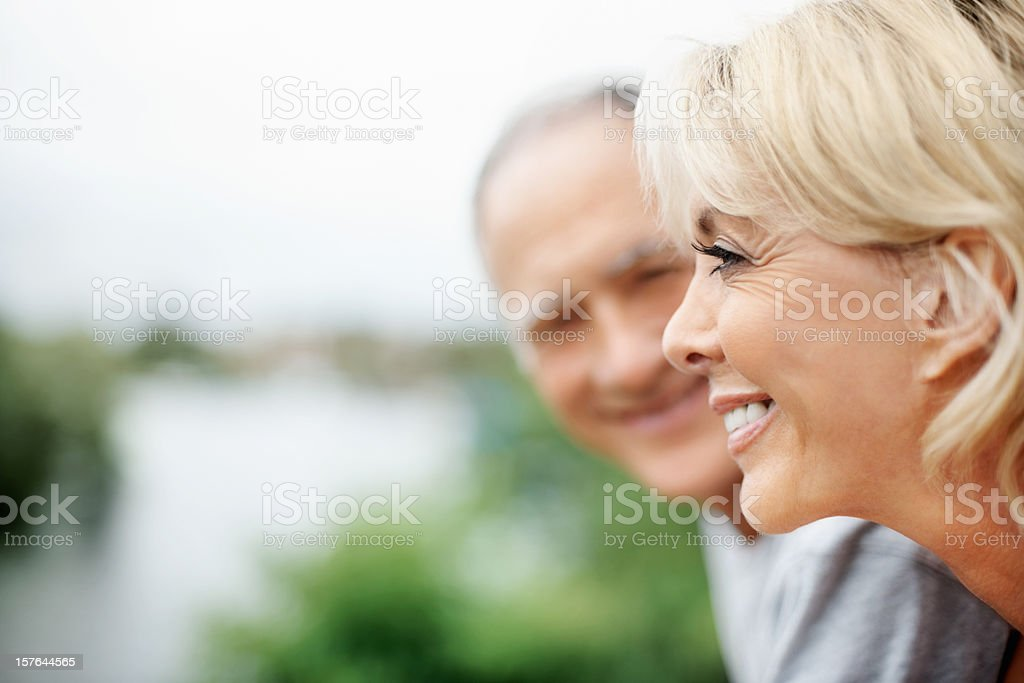 Smiling mature woman with husband looking at her royalty-free stock photo