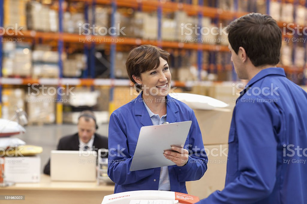 Smiling mature woman writing on clipboard stock photo