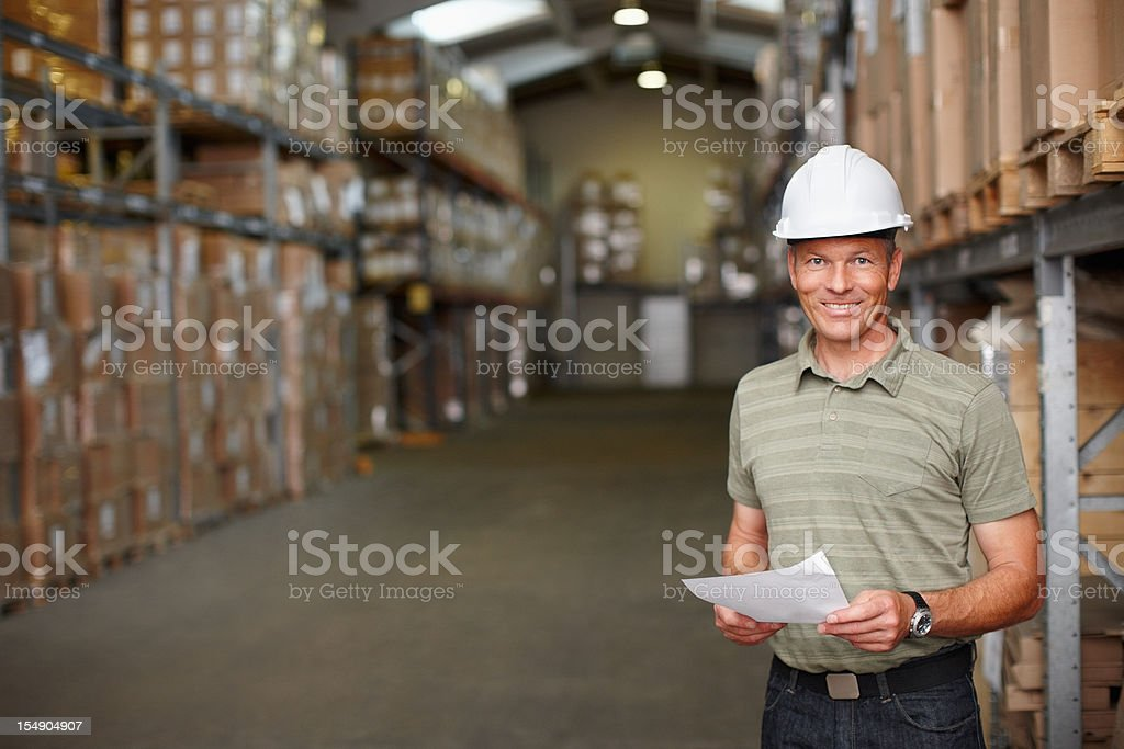Smiling mature worker standing with report at the warehouse depot royalty-free stock photo