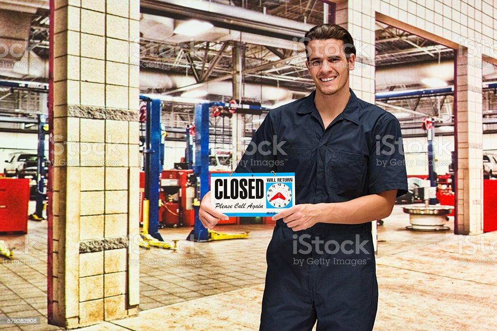 Smiling mechanic holding closed sign stock photo