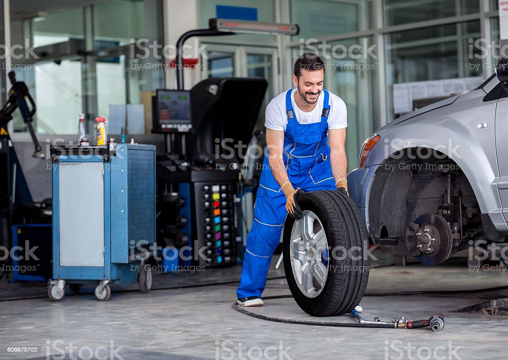 Smiling mechanic pushes the tire stock photo