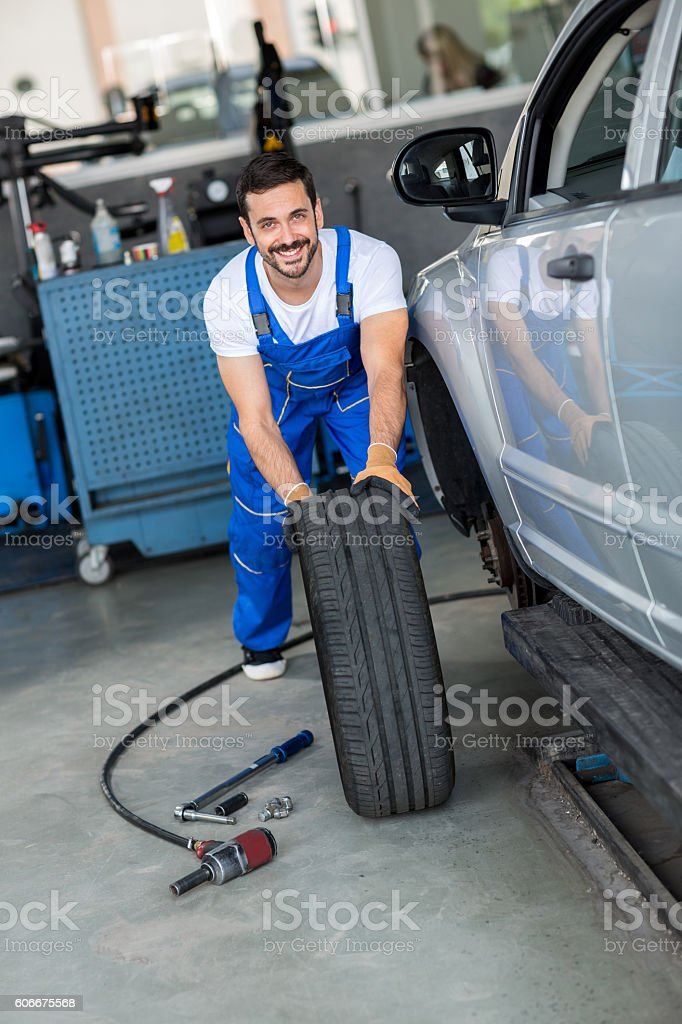 smiling mechanic repair and  pushing a black tyre stock photo