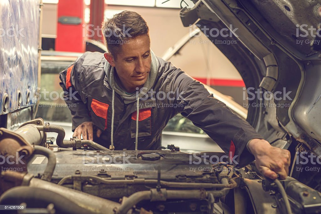 Smiling mechanic repairing a truck engine in auto repair shop. stock photo