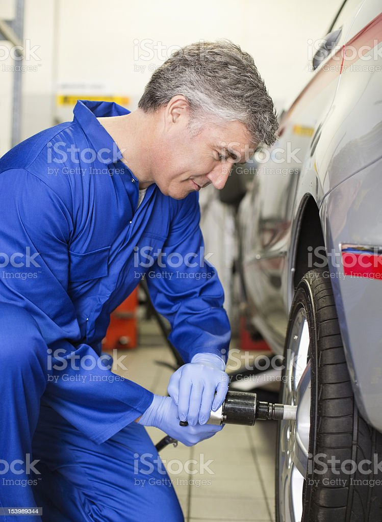 Smiling mechanic tightening lug nuts on car in auto repair shop stock photo