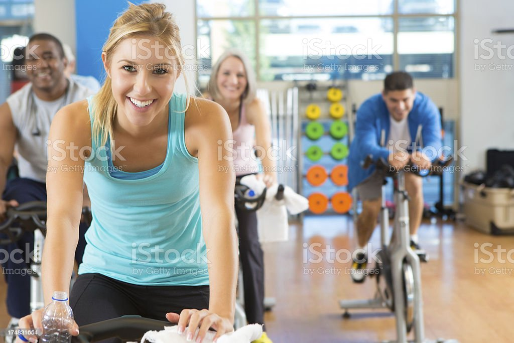 Smiling men and women on exercise bikes a gym royalty-free stock photo