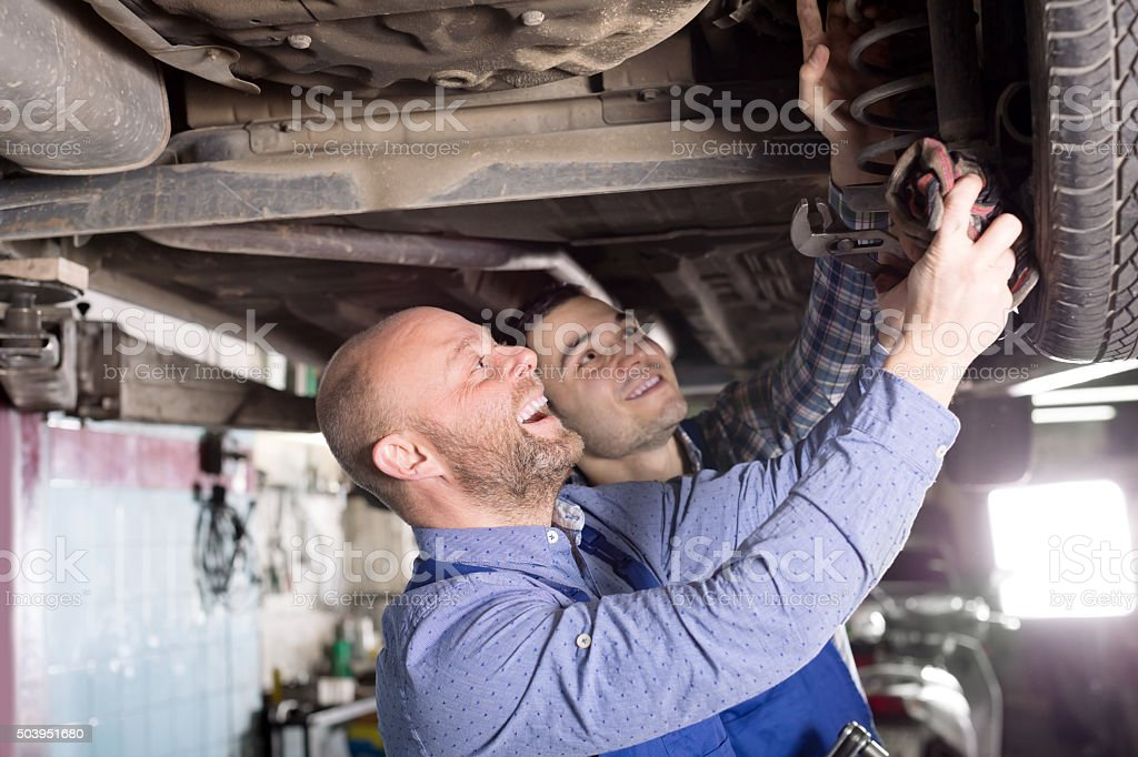 Smiling men in coveralls working stock photo