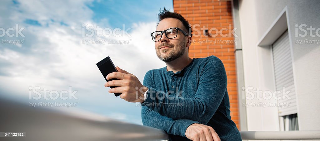 Smiling men typing text message stock photo