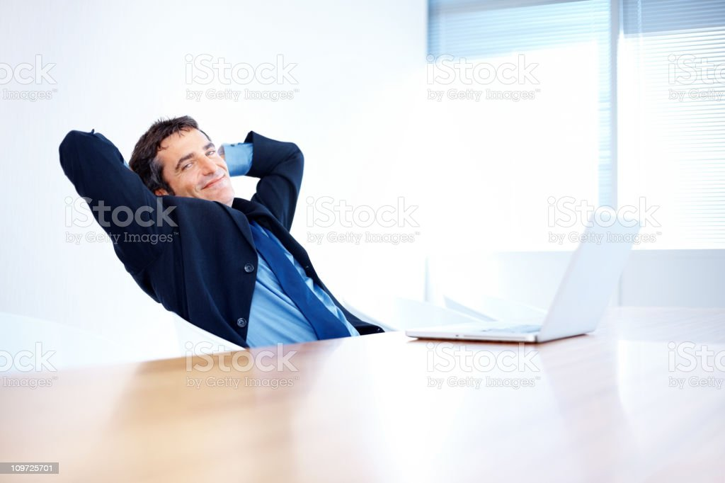 Smiling mid adult businessman taking a break after work royalty-free stock photo