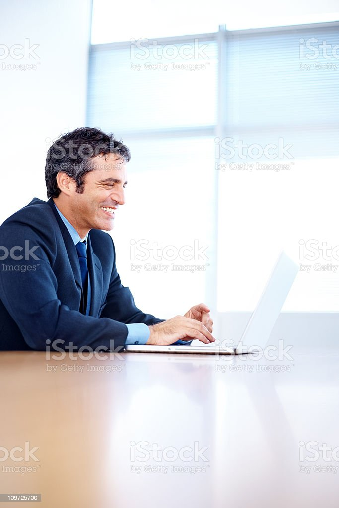 Smiling mid adult businessman working on a laptop royalty-free stock photo