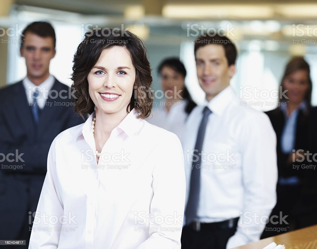 Smiling mid adult businesswoman with colleagues in the background royalty-free stock photo