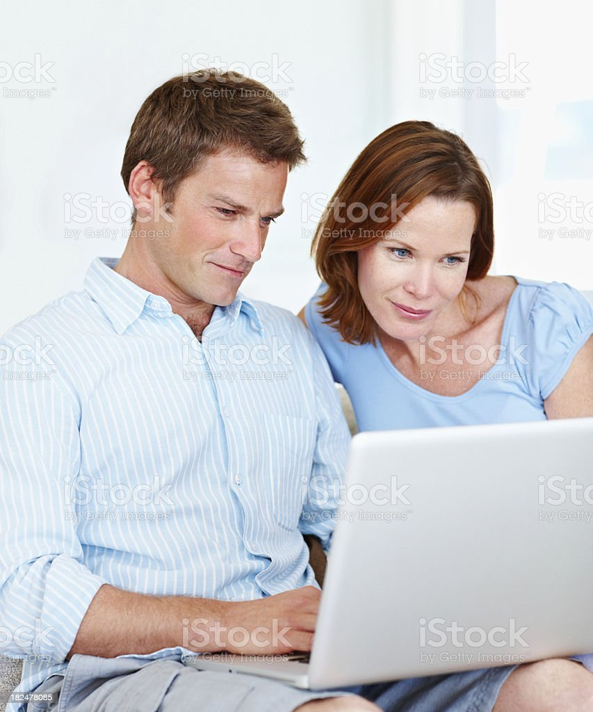 Smiling mid adult couple using laptop at home royalty-free stock photo