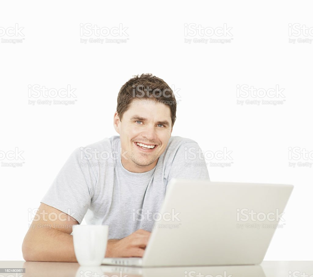 Smiling mid adult guy using a laptop over white royalty-free stock photo