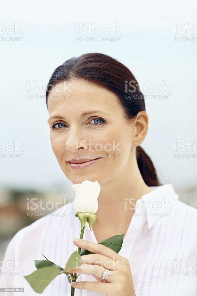 Smiling mid adult lady holding a flower royalty-free stock photo