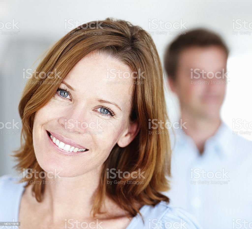 Smiling mid adult lady with man in the background royalty-free stock photo
