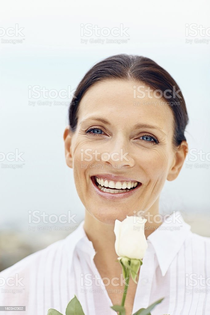 Smiling mid adult woman holding a flower royalty-free stock photo