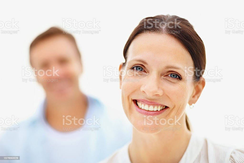 Smiling mid adult woman with husband in the background royalty-free stock photo